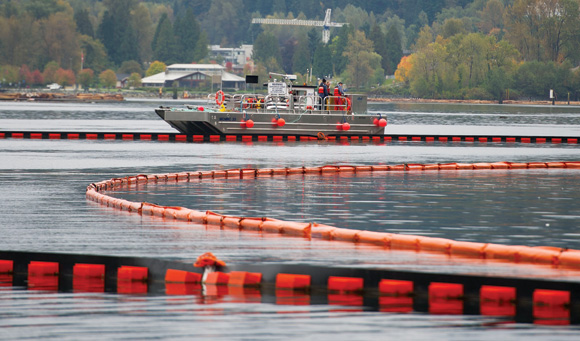 A Western Canada Marine Response Corp. primary containment barge, which transfers recovered oil to a larger tank barge, deploys  an oil-containment­ boom in Burrard Inlet, a fjord separating Vancouver from the North Shore, also reaches Burnaby and Port Moody.