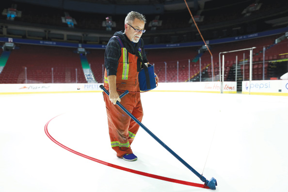 Once several layers of ice are created, followed by a layer of bright white paint, then Steve Caron can get to work painting a perfect faceoff circle. After creating the lines and logos, crews will work for another two days spraying water layers­ to create the final smooth polycrystal plane.