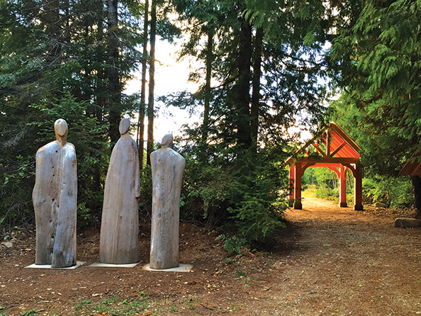 The simple archway, as well as the three-figure cedar sculpture called The Ancestors, created by Michael Dennis, mark the natural burial cemetery on Denman Island, BC.