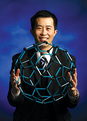Michael Ng holds a model of buckminsterfullerene, a molecule­ that has a fused-ring structure.