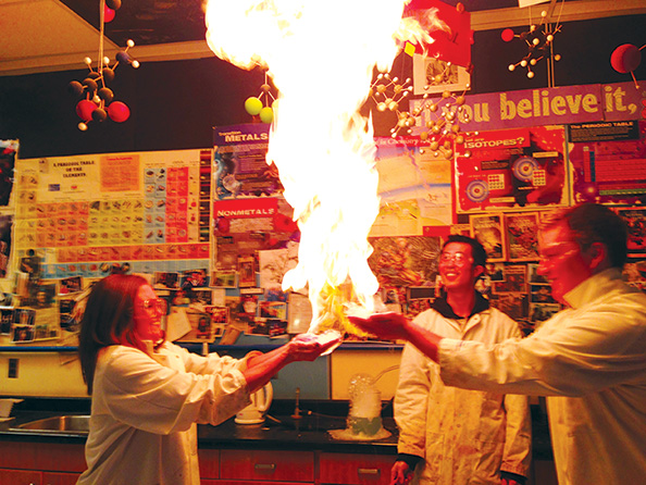 Michael Ng watches students burn methane gas captured in soapy water. Water has a high specific heat capacity, which protects their hands.