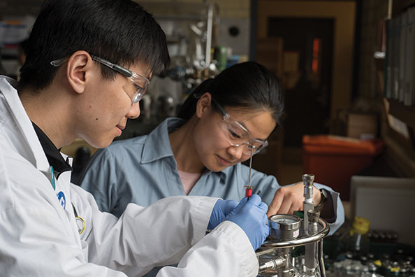 U of T graduate student Johnny Xiao with post-doctoral fellow Fei Luo check a bioreactor containing microbes that break down benzene anaerobically.