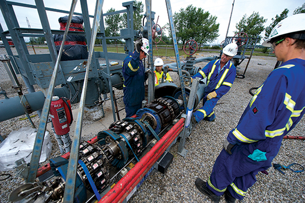 Alberta oilfield technicians install a mechanical scrubber, called a pig, that helps clean bacteria out of pipelines.