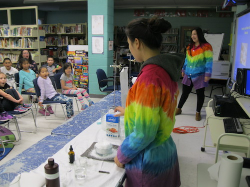 Lee performing a captivating demonstration of new chemical materials to the Grade 2 class at Jens Havens Memorial School, Nain, while Andersen talks through what is happening.