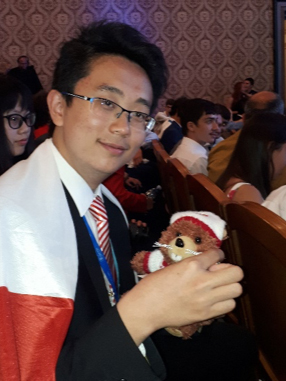 Aaron Dou at the closing ceremony with Nydus, the Canadian mascot