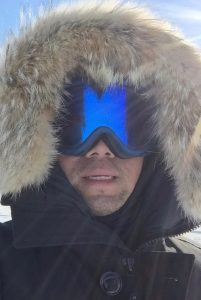 Feiyu Wang wearing a hood trimmed in fur and a large pair of reflective winter goggles.